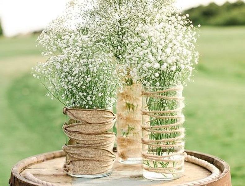 Floreros en frascos de vidrio